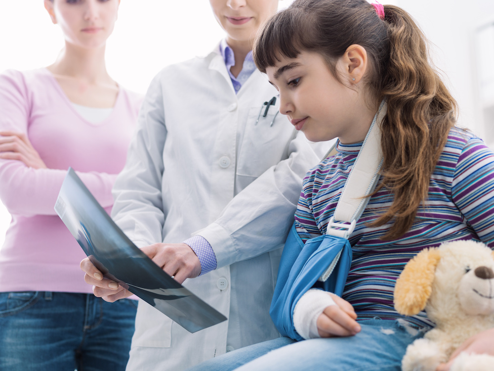 doctor showing young girl in sling x-rays